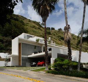 墨西哥高尔夫俱乐部里的斜坡豪宅 纯白外墙的住宅拥有温暖而明亮的内部装饰